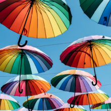 Umbrellas in rainbow color on blue sky background